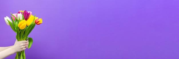 Букет тюльпанов в руках на фиолетовом фоне