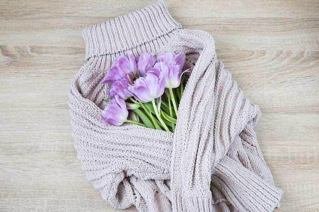 チューリップの花束は、粗いニットのウールのセーターで包まれています
