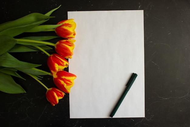 튤립 꽃다발은 흰색 시트와 비문을 위한 펜 근처의 어두운 배경에 놓여 있습니다