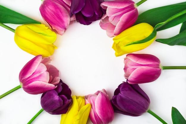 Букет тюльпанов из розовых, желтых и фиолетовых цветов, образующих рамку для текста. вид сверху. место для текста. белый фон