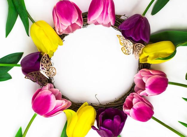 ピンク、黄色、紫の花のチューリップの花束と金色の蝶がテキストのフレームを形成しています。上からの眺め。テキストの場所。白色の背景