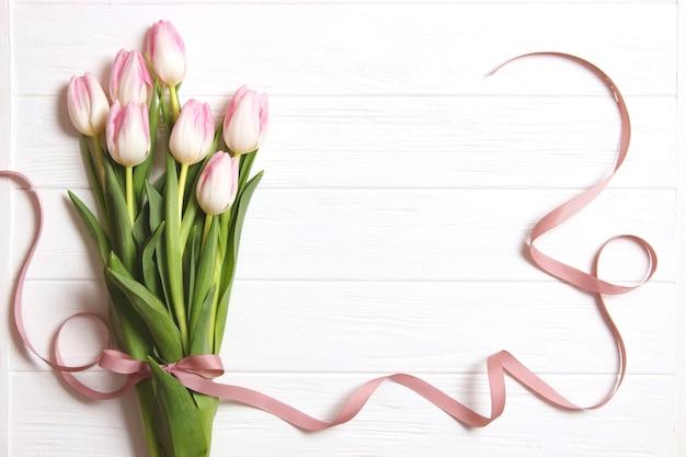 木製の背景の上のチューリップの花束上面図春の背景