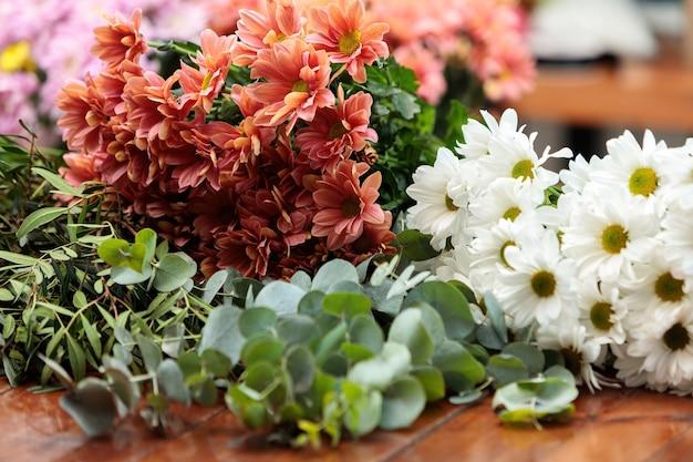 흰색과 붉은 국화의 꽃다발은 나무 테이블에 놓여 있습니다.