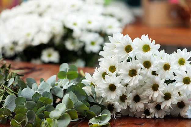 흰 국화 꽃다발은 나무 테이블에 놓여 있습니다.