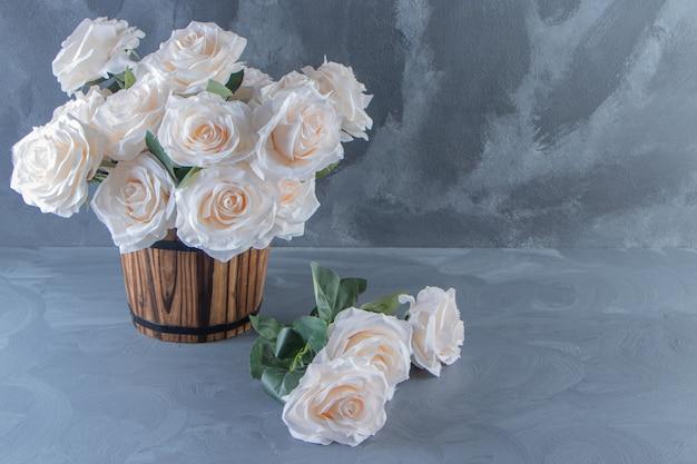 白いテーブルの上に、バケツの中の白い花の花束。