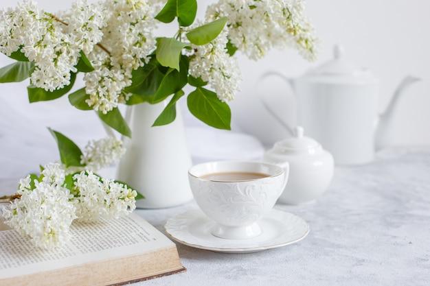 白いライラックの花束、一杯のコーヒーと古い本