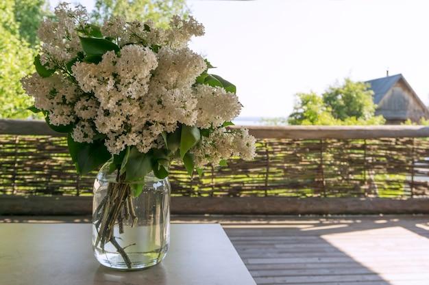 村の家のベランダのテーブルの上のガラスの瓶に白いライラックの花束