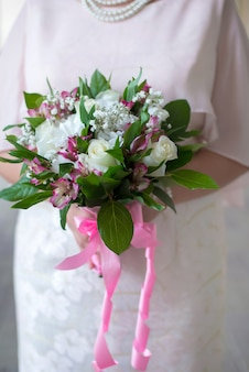 Букет из белых роз в женских руках крупным планом