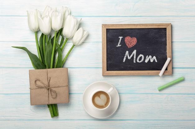 Букет из белых тюльпанов, чашка кофе с меловой доски и конверт на синих деревянных досках. день матери