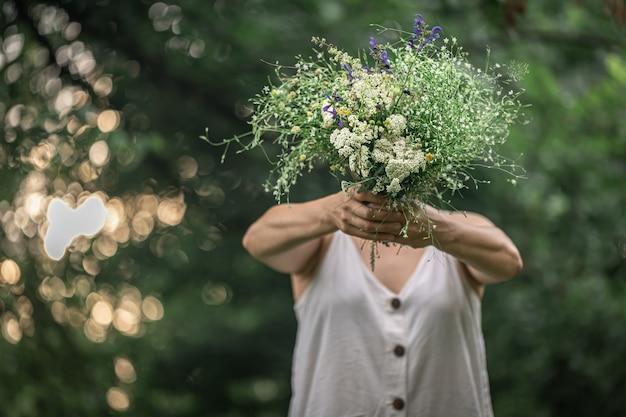 Букет полевых цветов в руках девушки на размытом фоне в лесу.