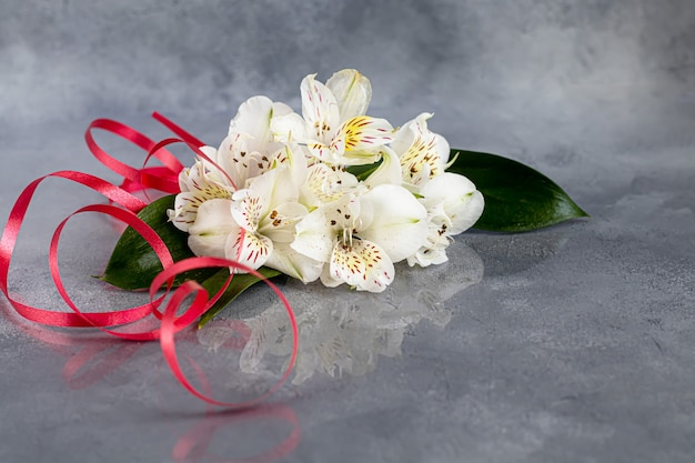 리본으로 장식 된 밝은 배경에 야생 난초의 꽃다발. 어머니의 날, 여성의 날, 발렌타인 데이 또는 생일. baner. 공간을 복사하십시오.