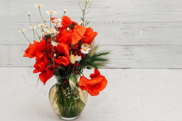 야생화 꽃다발: 투명한 유리 꽃병에 담긴 데이지와 양귀비