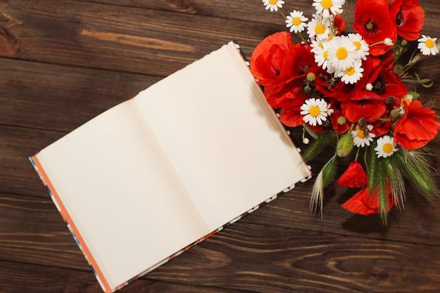 야생화 꽃다발: 공책이 있는 나무 탁자에 있는 데이지와 양귀비.
