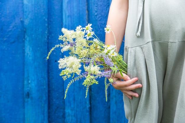 Букет полевых цветов в кармане летнего комбинезона.