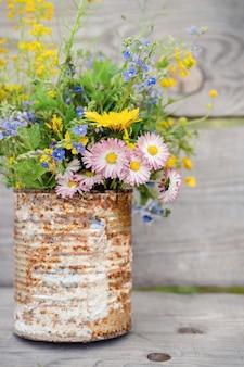 木の板に対してさびた素朴な瓶の中の野花の花束。