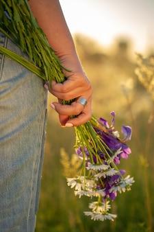 女性の手に野花の花束。日没。