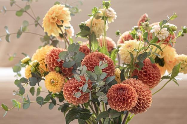 ぼやけた背景、クローズアップの黄色とオレンジ色の菊の花束。