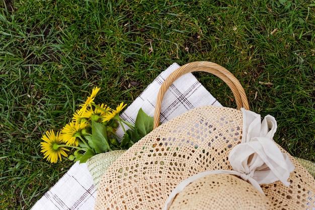 緑の芝生の上に黄色い花の花束、麦わら帽子、麦わらバッグが横たわっています。上面図。