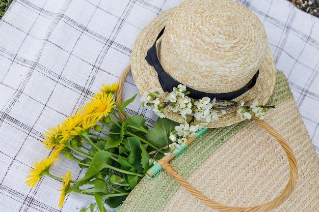 黄色い花の花束、麦わら帽子、麦わらバッグがテーブルクロスの上に横たわっています。上面図。