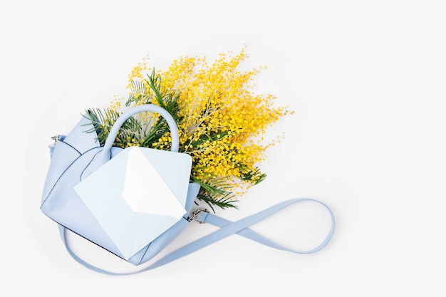 女性のハンドバッグに黄色い花の花束とはがきの封筒。フラットレイ、上面図。春のコンセプト