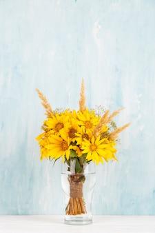 黄色の花、ヒマワリ、青のガラス花瓶に花束。コピースペース。