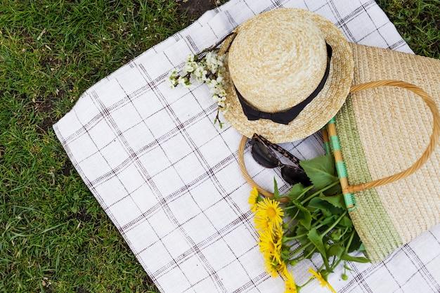 黄色い花のサングラスと麦わら帽子の花束、わら袋さくらの枝がテーブルクロスの上にあります。上面図。