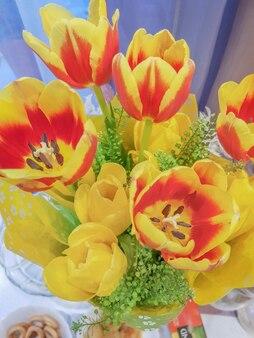 黄赤色の新鮮な春のチューリップの花束、上面図、垂直フレーム。