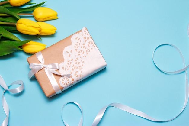 Букет из желтых тюльпанов и подарок крафт-бумаги украшен кружевной салфеткой на фоне голубой бумаги.