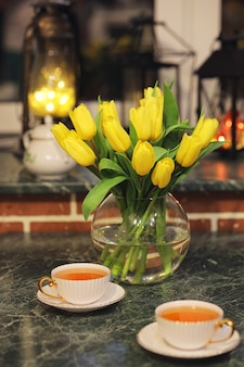 レトロな部屋のインテリアの花瓶に黄色いチューリップの花束。チューリップの花束とレトロなインテリア。