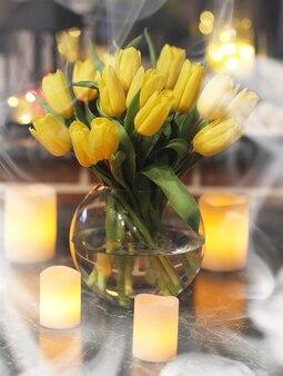 복고풍 방의 내부에 있는 꽃병에 노란 튤립 꽃다발. 튤립의 부케와 레트로 인테리어입니다.