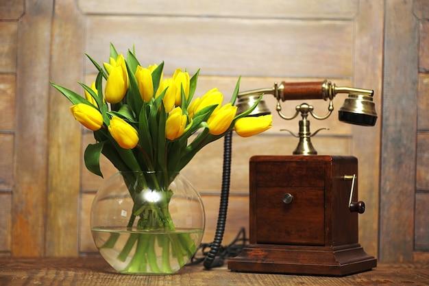 床の花瓶に黄色いチューリップの花束。黄色いチューリップの花から女性の日への贈り物。壁に花瓶の美しい黄色い花。