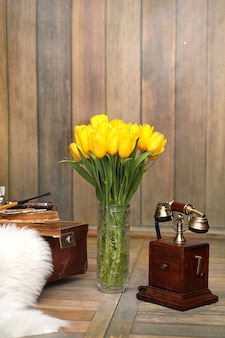 복고풍 방의 내부에 있는 꽃병에 노란 튤립 꽃다발. 튤립 오래 된 전화와 가방의 부케와 레트로 인테리어.