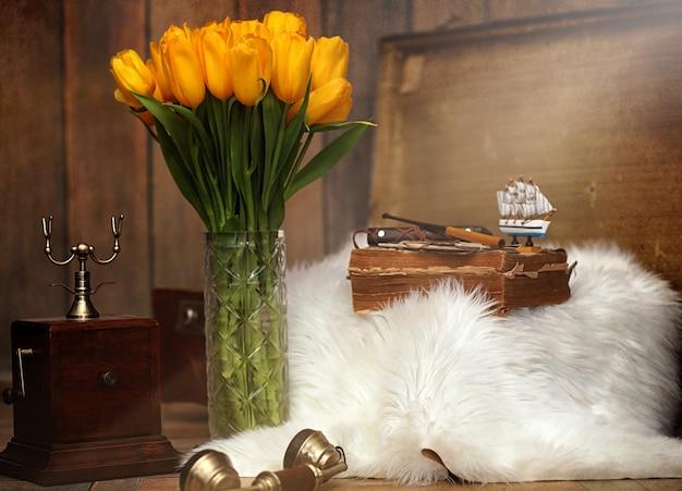 Букет желтых тюльпанов в вазе в интерьере ретро-комнаты. ретро интерьер с букетом тюльпанов, старый телефон и чемодан.