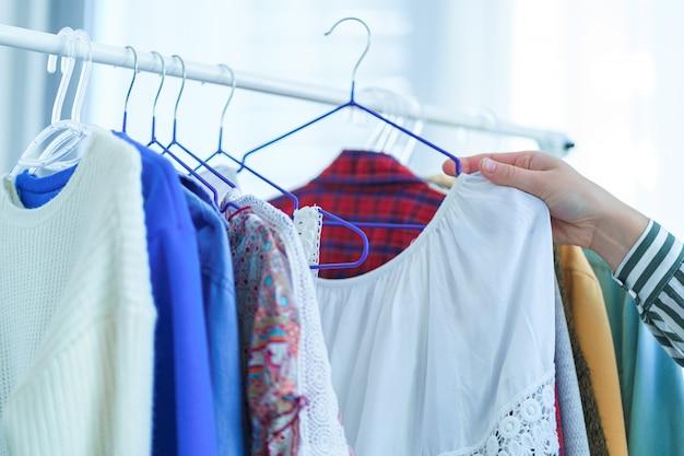 ハンガーにファッショナブルでスタイリッシュな服を着たブティック。流行の服やドレスの購入とショッピング