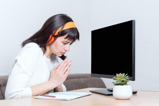 Кланяющаяся женщина в белом свитере и наушниках, сидящая за столом, смотрит на монитор с пустым черным экраном и показывает знак благодарности, признательности, сложив ладони вместе