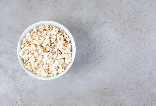 Чаша, полная хрустящего попкорна на мраморном фоне. фото высокого качества