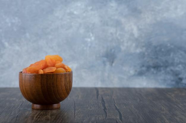 木製のテーブルの上に健康的なドライアプリコットフルーツがいっぱい入ったボウル。