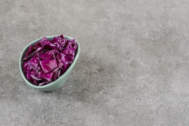 돌 배경에 잘라 붉은 양배추의 더미의 전체 그릇.