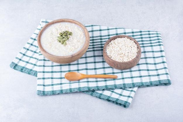 Чаша, полная сырого овса, и миска овсянки, посыпанная пепитасом, рядом с ложкой на полотенце на мраморной поверхности.