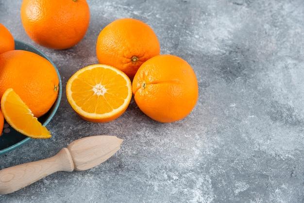 スライスしたジューシーなオレンジフルーツと木製のリーマーがいっぱい入ったボウル。