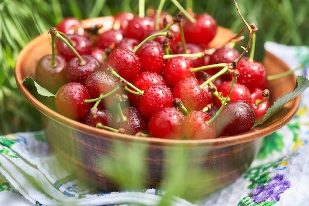 Чаша, полная сладких спелых красных вишен, стоящих на зеленой траве.