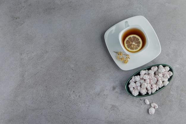 石のテーブルの上に熱いお茶のガラスのカップと甘い白いキャンディーでいっぱいのボウル。