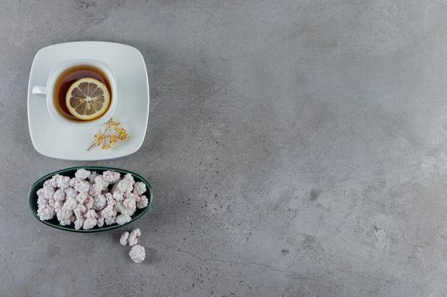 돌에 뜨거운 차 한잔과 함께 달콤한 흰색 사탕으로 가득한 그릇