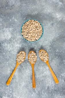 木のスプーンで白インゲン豆をいっぱい詰めたボウル