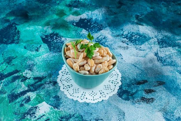 파란색 배경에 코스터에 구운 된 콩의 그릇.