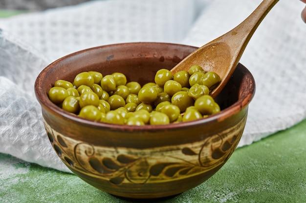 緑のテーブルの上に木のスプーンでゆでたグリーンピースのボウル。