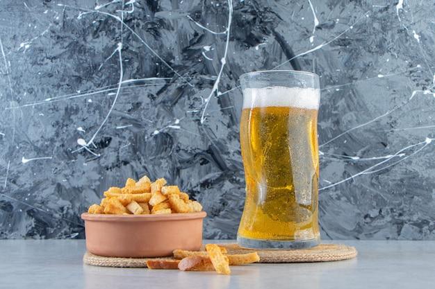 大理石の背景に、トリベットのグラスにパン粉とビールのボウル。