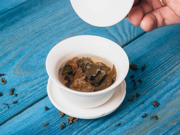 青い木製の背景に淹れたてのお茶のボウル。手がボウルの蓋を持ち上げます。大葉茶の開いた葉。チャイニーズティー。お茶会