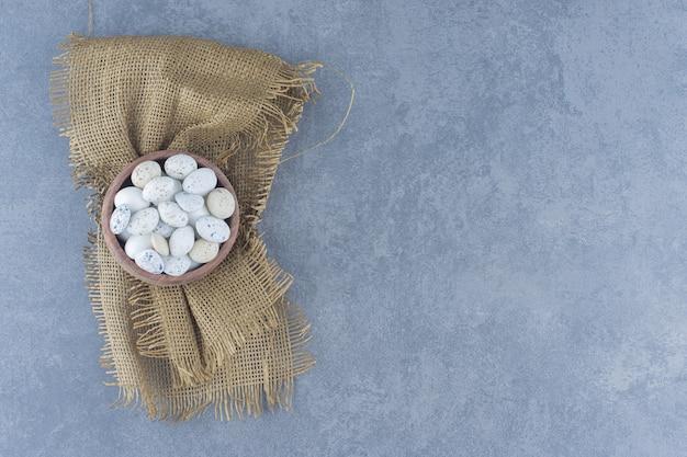 Ваза с конфетами на полотенце, на мраморном фоне.
