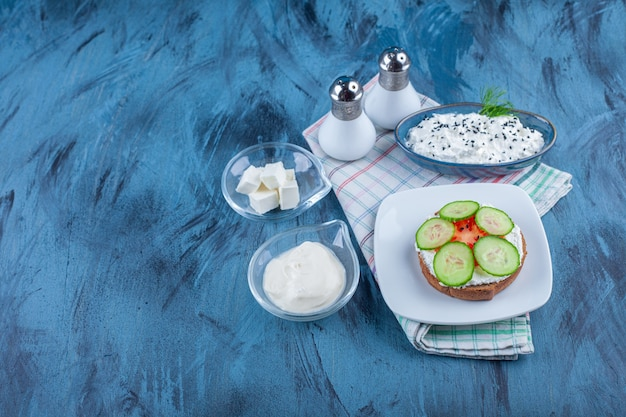 青い背景の上のタオルの上の皿の上のチーズパンの横にあるチーズのボウル。